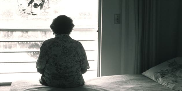 Elderly woman Sitting On Her Bed Looking Out Window