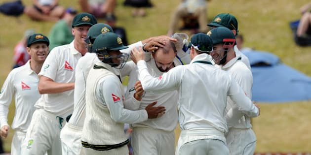 Australia's Nathan Lyon, centre, surrounded by team mates after bowling New Zealand's BJ Watling for 10 on the fourth day of the first International Cricket Test match at Basin Reserve, Wellington, New Zealand, Monday, Feb 15, 2016. (Ross Setford/SNPA via AP) NEW ZEALAND OUT