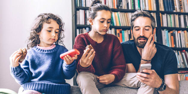 bearded father and two daughters on sofa looking together at mobiles