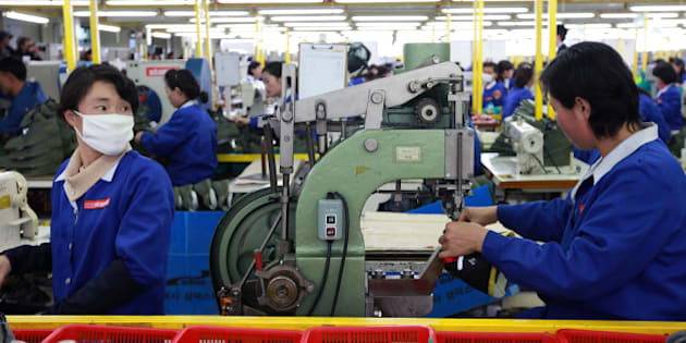 KAESONG, NORTH KOREA - DECEMBER 19:  North Korean employees work at the assembly line of the factory of South Korean company at the Kaesong industrial complex on December 19, 2013 in Kaesong, North Korea. North Korea agreed on this rare cross-border trip of about 30 foreign officials and financial experts proposed by South Korea as the South Korean government watches on Pyongyang following the execution of leader Kim Jong-Un's uncle, Jang Song-Thaek. The Kaesong Industrial Complex was re-opened in September after a five-month closure caused by military tensions.  (Photo by Park Jin-Hee-Pool/Getty Images)