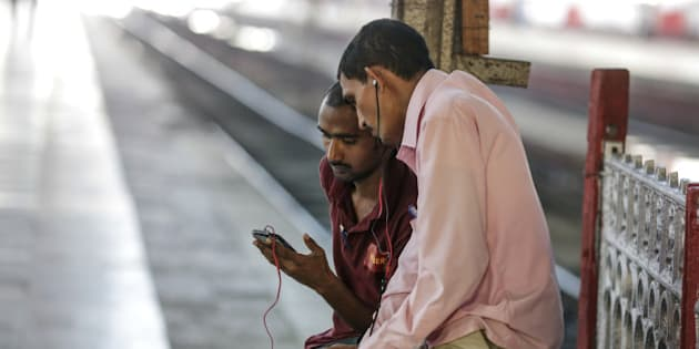 A passenger shows his smartphone screen to another passenger at Mumbai Central railway station in Mumbai, India, on Friday, Jan. 22, 2016. Google Inc. in partnership with RailTel Corp. and Indian Railways today launched high speed WiFi at the station. They plan to roll out the service to more than 400 railway stations, covering 10 million passengers each day, according to chief executive officer Sundar Pichai. Photographer: Dhiraj Singh/Bloomberg via Getty Images