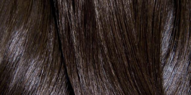 Tight crop of shiny dark brown hair.