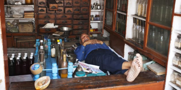 An Indian pharmacist sleeps in his small shop at midday. He is surrounded by cabinets and shelves stocked with drugs and ingredients he can make into medicines and lotions and potions using the pestle and mortar and scales