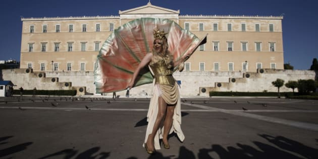 A Drag Queen performer poses for photos during a Gay Pride event march past the Tomb of the Unknown Soldier in front of the Greek Parliament  in central Athens, Greece, on Saturday, June 9, 2012. About 1,000 people took part in the march. (AP Photo/Kostas Tsironis)