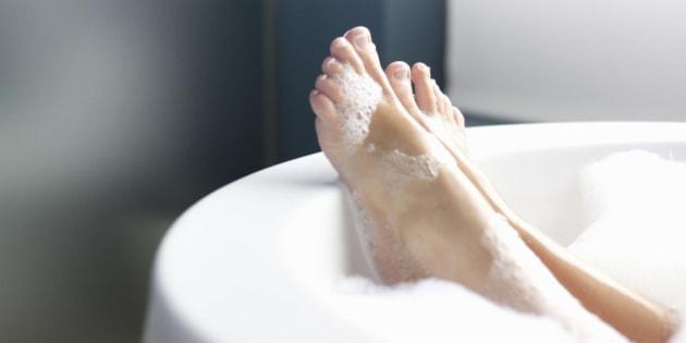 Feet resting on edge of tub as woman lays in a foam bath in a luxury hotel