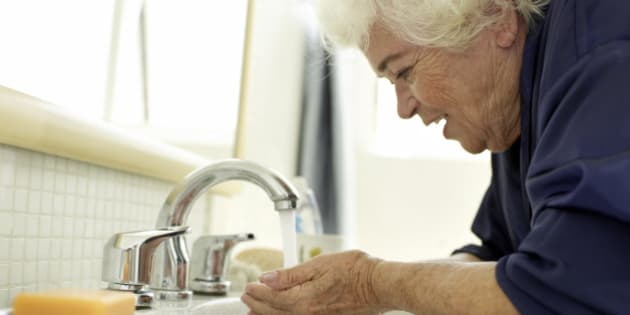 Elderly woman washing her face after wake up