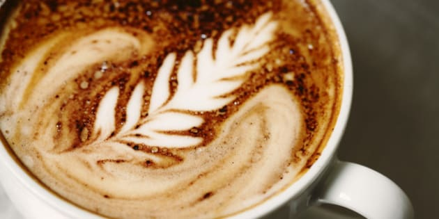 'A delicious cup of cafe mocha espresso on a stainless steel surface, beautifully poured with a signature rosette cream pattern.'