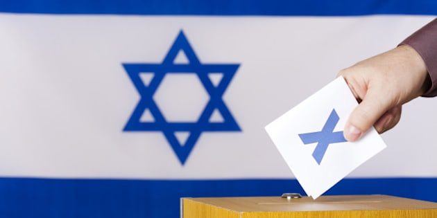 Hand inserting a ballot to ballot box. Flag of Israel in the background.