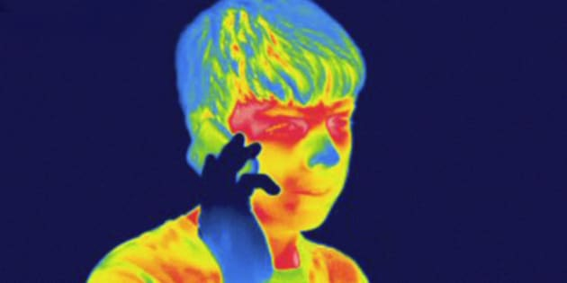 Thermogram of a male teenager talking on a cell phone. The temperature scale runs from white (warmest) through red, yellow, green and cyan, blue and black (coldest).
