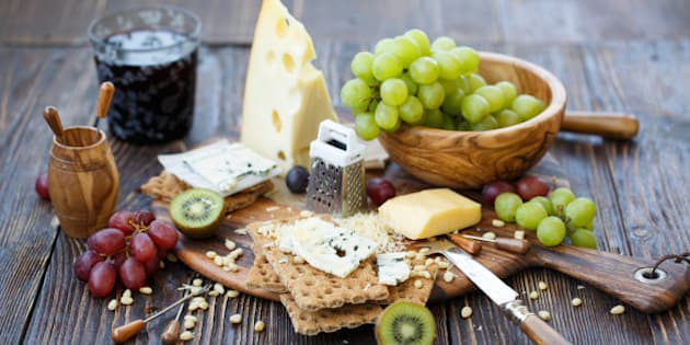 Breakfast with crackers, blue cheese, grape, kiwi, nuts and glass of wine on old rustic board with knife and stickers lying around