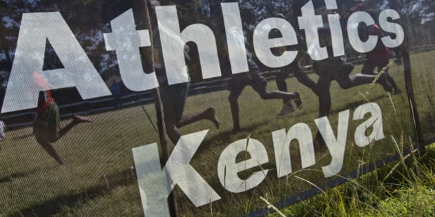 In this photo taken Sunday, Jan. 31, 2016, junior athletes run past a sign for Athletics Kenya at the Discovery cross country races in Eldoret, western Kenya.  Two Kenyan athletes, Joy Sakari and Francisca Koki Manunga, who are serving a four-year ban for doping at the 2015 world championships say the chief executive of Athletics Kenya Isaac Mwangi, the country's governing body for track and field, asked them each for a US dlrs 24,000 bribe to reduce their suspensions. (AP Photo/Ben Curtis)