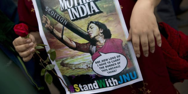 An Indian student carries a flower and holds a poster during a protest at the Jawaharlal Nehru University or JNU against the arrest of a student union leader in New Delhi, India, Thursday, Feb. 18, 2016. Scenes of protest that rocked a New Delhi university this week spread across the country Thursday, with students and teachers from cities including Bangalore, Kolkata and Chennai joining demands for the release of a student leader arrested on sedition charges. (AP Photo/Tsering Topgyal)