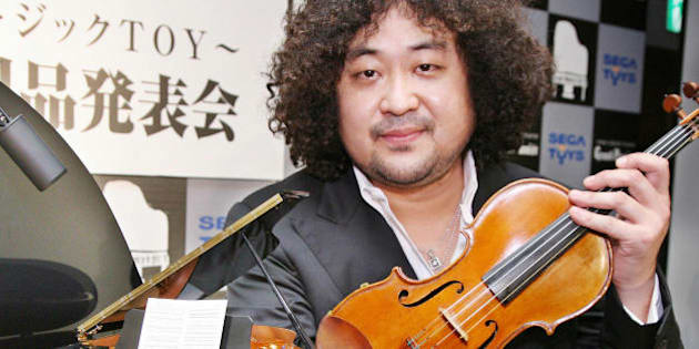 Tokyo, JAPAN:  Japanese violinist Taro Hakase poses next to the world's smallest grand piano 'Grand Pianist', produced by Japan's toy maker Sega Toys, which have 88 working keys and can automatically play 100 pre-installed music songs after his session with auto-play piano in Tokyo 29 November 2006. The one sixth scaled grand piano will go on sale 01 April 2007 with a price of 47,000 yen (400 USD).    AFP PHOTO / Yoshikazu TSUNO  (Photo credit should read YOSHIKAZU TSUNO/AFP/Getty Images)