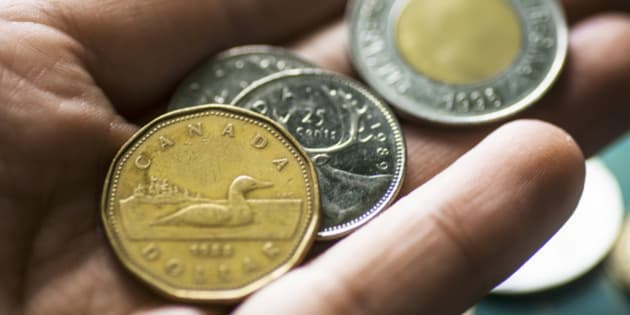 Some canadian dollar coins in a human hand