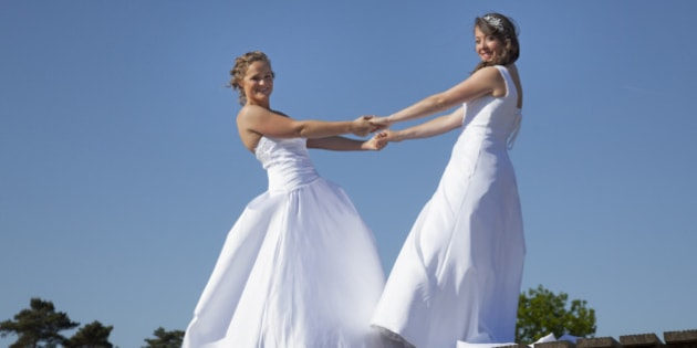 two brides on wooden bridge against blue sky background hold each other