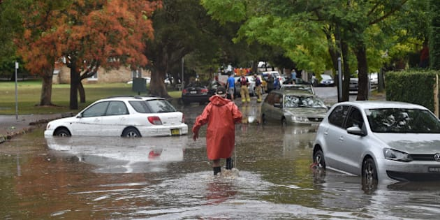 A worker wades past inundated cars on a flooded street after a storm in the eastern suburbs of Sydney on December 16, 2015. Sydney was smashed by a tornado-like storm with hail as big as golf balls and winds gusting at 200 kilometres (124 miles) an hour causing havoc with two people requiring treatment -- one for shock and one for a head wound -- in the hardest-hit suburb of Kurnell, an ambulance official said. AFP PHOTO / Peter PARKS / AFP / PETER PARKS        (Photo credit should read PETER PARKS/AFP/Getty Images)