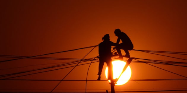 Indian workers adjust electricity cables set up temporarily on the banks of the river Ganga in preparation for the annual Hindu religious fair of Magh Mela in Allahabad on December 26, 2015. The Magh Mela is held every year on the banks of Triveni Sangam - the confluence of the three great rivers Ganga, Yamuna and the mystical Saraswati during the Hindu month of Magh which corresponds to mid January - mid February. AFP PHOTO/ SANJAY KANOJIA / AFP / Sanjay Kanojia        (Photo credit should read SANJAY KANOJIA/AFP/Getty Images)