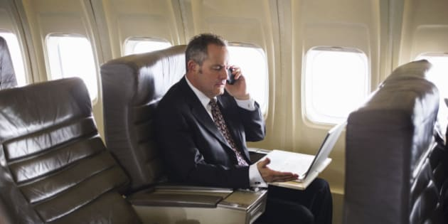 man wearing suit using cell phone on airplane