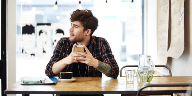 Guy with phone relaxing in coffee shop