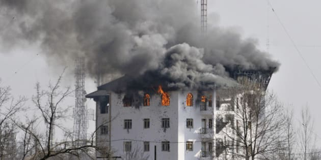 SRINAGAR, INDIA - FEBRUARY 22: Columns of smoke come out from the top floor of Entrepreneurship Development Institute building in which militants were holed up during a gunfight on February 22, 2016 in Sempora, Pampore on the outskirts of Srinagar, India. Three militants barged into the institute building on Saturday soon after attacking a convoy of security forces, leaving three CRPF jawans dead and eight injured. One civilian, Abdul Gani Mir died after sustaining a bullet injury later. (Photo by Waseem Andrabi/Hindustan Times via Getty Images)