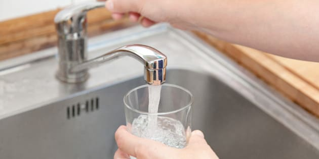 woman holding glass at water tap and filling water.