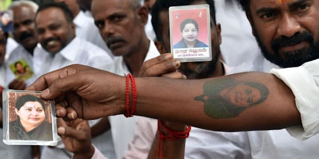 Supporters of India's former southern Tamil Nadu state chief minister J. Jayalalithaa display her photographs and an arm tattooed with her portrait as they wait outside the Bangalore Central Jail for her release on bail in Bangalore on October 18, 2014. India's top court granted bail October 17 to a powerful south Indian film star-turned-politician jailed last month for corruption, a ruling that sparked jubilation in her home state. Jayalalithaa Jayaram, 66, an ex-film star and a longtime head of Tamil Nadu, was convicted last month of having land, gold and other assets vastly exceeding her income in a case that had dragged on for nearly two decades, and sentenced to four years in jail. AFP PHOTO/Manjunath KIRAN        (Photo credit should read MANJUNATH KIRAN/AFP/Getty Images)