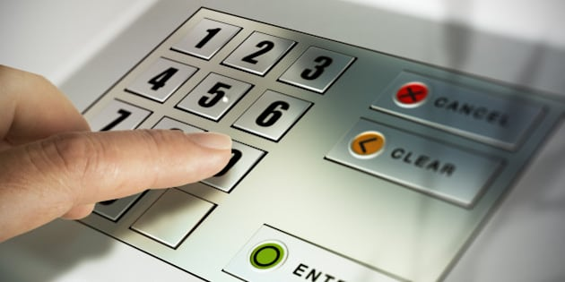 Finger about to press a pin code on a pad. Security code on an Automated Teller Machine, ATM