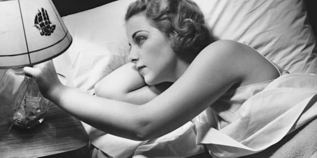 Young woman lying on bed, turning off lamp on night table (B&W), elevated view