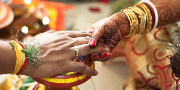 The Bride and the groom holding hands as a part of their wedding ceremony as seen in a traditional Bengali wedding. The 'Ghot' or earthen pitcher seen below is sacred and part of the ceremony.