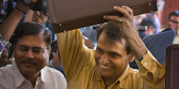 Indian Railway Minister Suresh Prabhu lifts the briefcase containing Railway budget for the year 2015-16 as he arrives at the parliament house to present it in New Delhi, India, Thursday, Feb. 26, 2015. Indian Railways is one of the world's largest and serves more than 23 million passengers a day. (AP Photo/Manish Swarup)