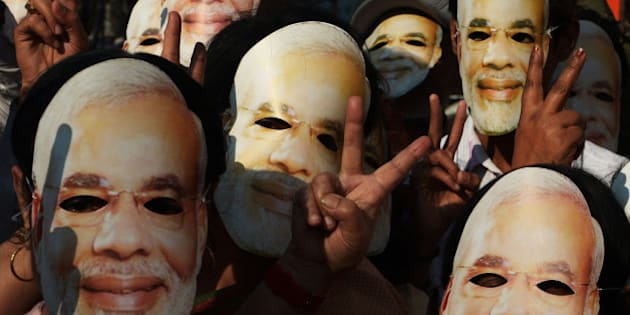 Bharatiya Janata Party (BJP) activists, clad in masks of BJP prime ministerial candidate and Gujarat state Chief Minister Narendra Modi, participate in a rally in Kolkata on February 1, 2014. Modi, tipped in opinion polls to be India's next premier, remains a polarising figure accused by critics of turning a blind eye to anti-Muslim riots in Gujarat in 2002 in which as many as 2,000 died. He has denied any wrongdoing. AFP PHOTO/Dibyangshu SARKAR        (Photo credit should read DIBYANGSHU SARKAR/AFP/Getty Images)