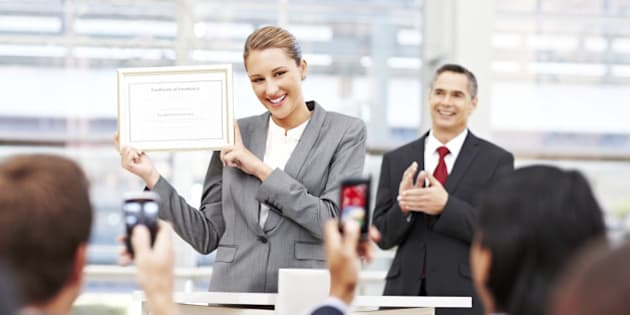 Attractive businesswoman receives applause on stage while holding up an award. Horizontal shot.