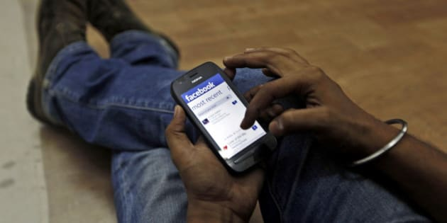 A man surfs the Facebook site on his mobile phone in Mumbai, India, Friday, May 18, 2012 . Facebook's stock is set to begin trading on the Nasdaq Stock Market on Friday, the day after the world's definitive online social network raised $16 billion in an initial public offering that valued the company at $104 billion. (AP Photo/ Rajanish Kakade)