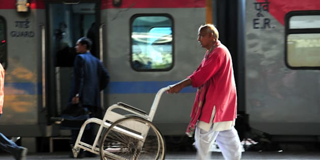 KOLKATA, INDIA - FEBRUARY 24: A porter carrying a wheel chair for assisting passengers at Howrah railway station on February 24, 2015 in Kolkata, India. (Photo by Indranil Bhoumik/Mint via Getty Images)