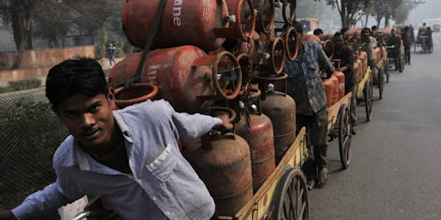 NEW DELHI INDIA  JANUARY 30: LPG cooking gas cylinder vendors transferring cylinders on a cart from a warehouse on January 30, 2014 in New Delhi, India. Cabinet approves raising ceiling on subsidized cooking gas cylinders from 9 to 12. (Photo by Vipin Kumar/Hindustan Times via Getty Images)