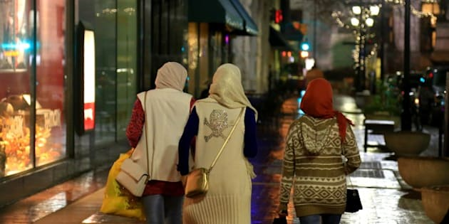 Young Muslim girls walk along the shopping district wearing Hijab and coats