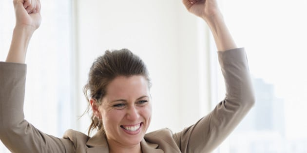 Portrait of cheering woman in office