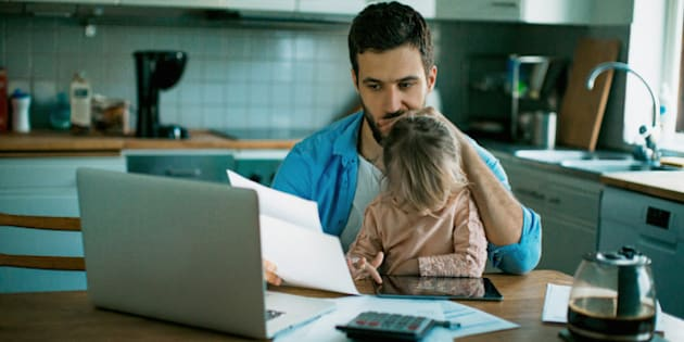 Photo of a father and daughter sitting in the kitchen,daughter is playing while dad is sitting worried and checking his bills