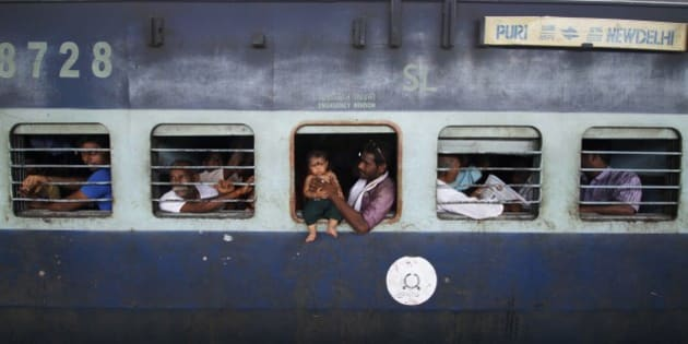 A child sits on the emergency exit window of a train, held by an adult, at a railway station in Puri, India, Tuesday, July 8, 2014. India's new rail minister Sadananda Gowda on Tuesday proposed allowing foreign investment to modernize the country's cash-strapped state railways. India has one of the world's largest railways, which transports 23 million passengers a day. Indian Railways is one of the world's biggest employers with more than 1.3 million employees. The network lost 300 billion rupees ($5 billion) last year. (AP Photo/Biswaranjan Rout)