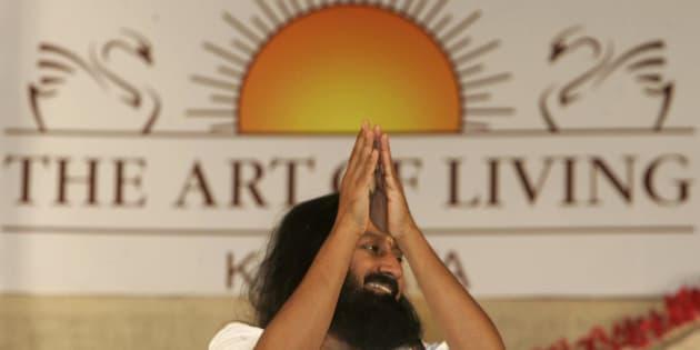 Indian spiritual guru and founder of The Art of Living Foundation Sri Sri Ravi Shankar greets followers as he arrives at a meditation camp in Calcutta, India, Saturday, Feb. 14, 2009. (AP Photo/Bikas Das)