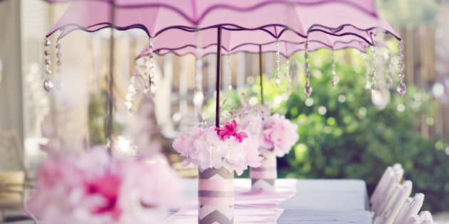 Table set for a baby shower for a girl. With pink umbrellas with crystals and pink flowers.
