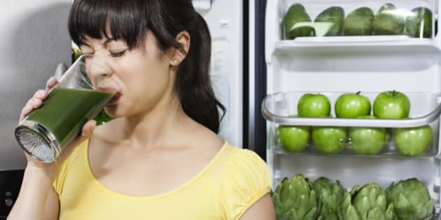Grimacing mixed race woman drinking healthy drink near refrigerator
