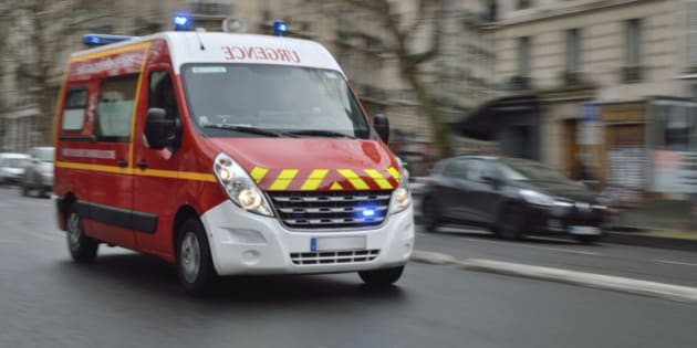 Red emergency vehicle speeding on Paris street