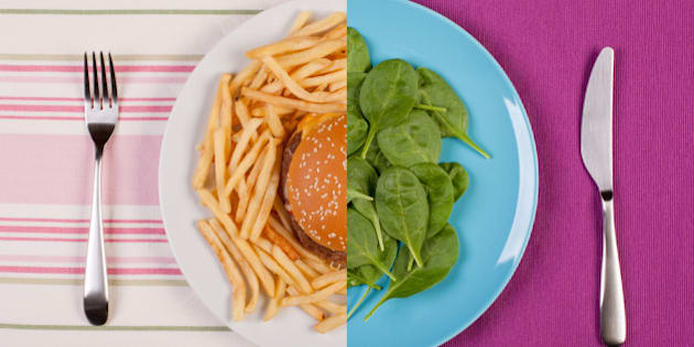 stock image of low fat healthy spinach leaves against unhealthy greasy burger with french fries. diet concept