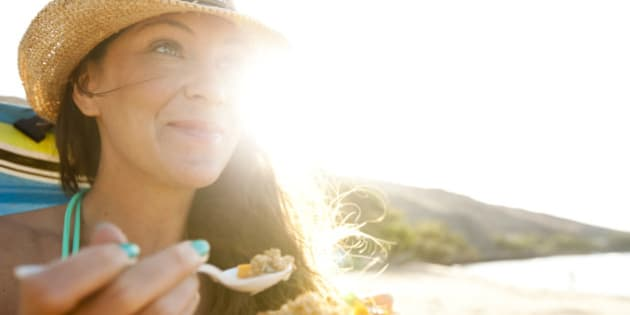 A beautiful woman with a straw hat eating a papaya with fresh granola and yogurt.
