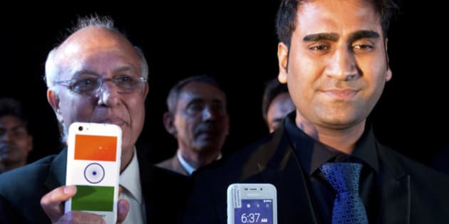 Mohit Goel, right, Director of Ringing Bells Pvt. Ltd., and Ashok Chadha, left, spokesperson, show a Freedom 251 smartphone, which is to be priced at Rs 251 or $3.6 approximately, during its release in New Delhi, India, Wednesday, Feb. 17, 2016.  (AP Photo/Saurabh Das)