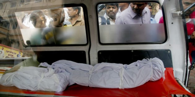 People look at the bodies of two among the victims fatally stabbed by a man as they are kept inside an ambulance outside a hospital in Thane, outskirts of Mumbai, India, Sunday, Feb. 28, 2016.A man in western India fatally stabbed 14 members of his family, including seven children, early Sunday before hanging himself, police said. (AP Photo/Rajanish Kakade)