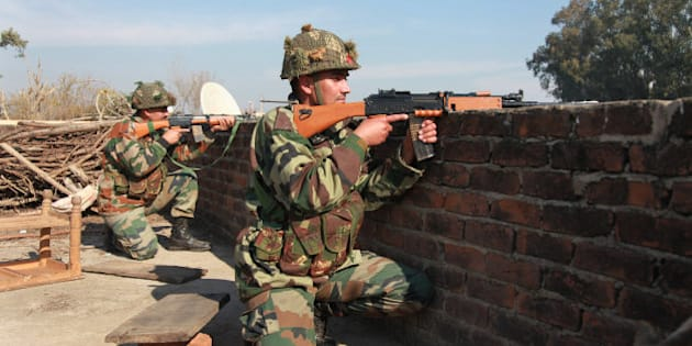 Indian army soldiers take positions on a rooftop of a building outside the Indian airbase in Pathankot, 430 kilometers (267 miles) north of New Delhi, India, Saturday, Jan. 2, 2016. At least four gunmen entered an Indian air force base near the border with Pakistan on Saturday morning and exchanged fire with security forces, leaving two of them dead, officials said. (AP Photo/Channi Anand)