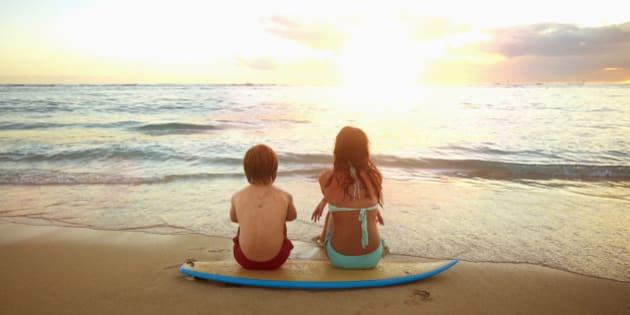 Caucasian children sitting on surfboard on tropical beach