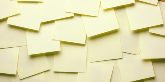 Lots of blank stick notes overlapping on cork board.